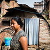 A woman in front of the temporary shelter where she still lives, two years after the earthquakes in Nepal.<br /> Pokhara, Nepal. March 2017<br /> -----------<br /> Une femme devant l'abri temporaire où elle vit encore, deux ans après les tremblements de terre au Népal.<br /> Pokhara, Népal. Mars 2017