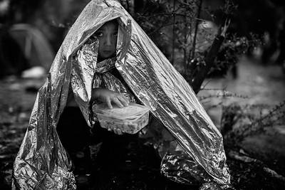 A young refugee girl hides from the rain under an emergency blanket in Moria refugee camp. Lesvos Island, Greece. October 2015. ----------- Une jeune fille réfugiée se protège de la pluie sous une couverture d'urgence dans le camp de réfugiés de Moria. Ile de Lesbos, Grèce. Octobre 2015.