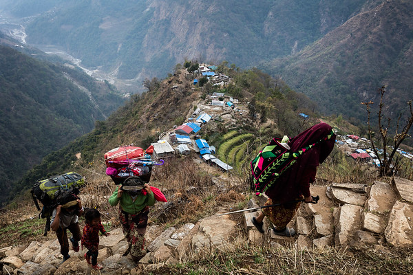 A group of villagers walk towards the village of Barpak high in the mountains of Gorkha. They carry supplies on their backs that are difficult to carry up there when the roads are closed.<br /> Barpak, Nepal. March 2017<br /> -----------<br /> Un groupe de villageois marche dans les montagnes en direction du village de Barpak. Ils transportent sur leurs dos de lourdes provisions, difficiles à acheminer lorsque les routes sont fermées.<br /> Barpak, Népal. Mars 2017