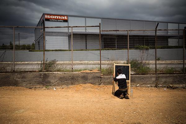 All by himself in a Greek refugee camp, a young boy write on a blackboard, playing as in a classroom.<br /> Oinofyta refugee camp, Greece. May 2016<br /> -----------<br /> Un jeune garçon tente par lui-même de simuler l'illusion d'une classe d'école en écrivant sur un tableau noir au milieu d'un camp de réfugiés.<br /> Oinofyta, Grèce. Mai 2016
