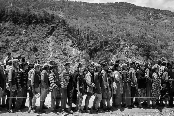 A line of villagers waiting to receive supplies provided by the Canadian NGO CECI minutes before the important aftershock of May 12th.<br /> Organization: CECI<br /> Gorkha, Nepal. May 2015.<br /> ---------<br /> Un groupe de villageois attendent en ligne pour recevoir des provisions fournies par l'ONG canadienne CECI, quelques minutes à peine avant la réplique importante du 12 mai.<br /> Organisme: CECI<br /> Gorkha, Népal. Mai 2015.