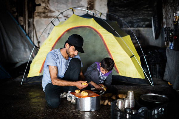 Father and son prepare food in front of their tent outside a refugee camp near the Macedonian border.<br /> Oinofyta refugee camp, Greece. May 2016<br /> -----------<br /> Un père et son fils préparent le repas devant leur tente installée en retrait d'un camp de réfugiés à la frontière macédonienne.<br /> Oinofyta, Grèce. Mai 2016