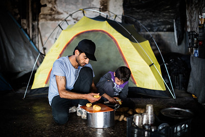Father and son prepare food in front of their tent outside a refugee camp near the Macedonian border. Oinofyta refugee camp, Greece. May 2016 ----------- Un père et son fils préparent le repas devant leur tente installée en retrait d'un camp de réfugiés à la frontière macédonienne. Oinofyta, Grèce. Mai 2016