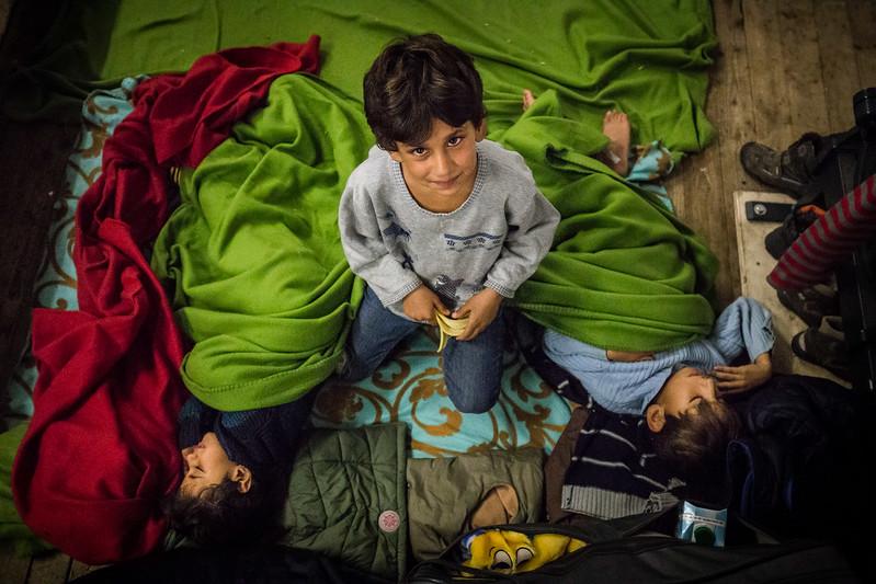 In a refugee camp in Berlin, the elder brother takes care of his younger siblings while they sleep on the floor.<br /> Berlin, Germany. November 2015.<br /> -----------<br /> Le frère ainé veille sur ses deux jeunes frères assoupis sur le plancher d'un camp de réfugiés à Berlin.<br /> Berlin, Allemagne. Novembre 2015.