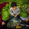 In a refugee camp in Berlin, the elder brother takes care of his younger siblings while they sleep on the floor.<br /> Berlin, Germany. November 2015.<br /> -----------<br /> Le frère ainé veille sur ses deux jeunes frères assoupis sur le plancher d'un camp de réfugiés à Berlin.<br /> Berlin, Allemagne. Novembre 2015.