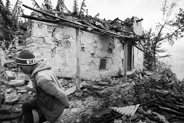 A man walks past his collapsed house that was damaged during the earthquake of April 25th in Nepal. The epicenter was located less than two hundred kilometers away.<br /> Gorkha, Nepal. April 2015.<br /> ---------<br /> Un homme marche devant sa maison effondrée suite au tremblement de terre du 25 avril au Népal. L'épicentre était situé à moins de deux cent kilomètres.<br /> Gorkha, Népal. Avril 2015.