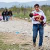 An Afghan man walks in the fields towards the transit camp of Gevgelija with his child in his arms and his family behind.<br /> Gevgelija, Macedonia. October 2015.<br /> -----------<br /> Un homme afghan marche dans les champs en direction du camps de transit de Gevgelija avec son enfant dans les bras et sa famille derrière.<br /> Gevgelija, Macédoine. Octobre 2015.