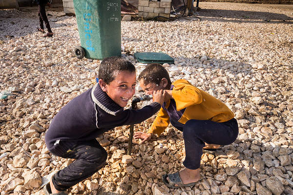 Children playing with water in a refugee camp at the Syrian border in Lebanon.<br /> Bekaa Valley, Lebanon. November 2015.<br /> -----------<br /> Des enfants jouent avec de l'eau dans un camp de réfugiés à la frontière syrienne au Liban.<br /> Vallée de la Bekaa, Liban. Novembre 2015.