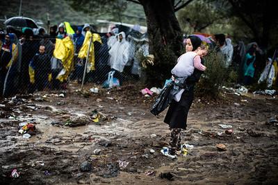 A mother holds and tries to protect her young daughter from the rain while waiting for registration under the rain in Moria refugee camp. Lesvos Island, Greece. October 2015. ----------- Une mère porte sa fille et tente de la protéger de la pluie dans l'attente du processus d'enregistrement dans le camp de réfugiés de Moria. Ile de Lesbos, Grèce. Octobre 2015.