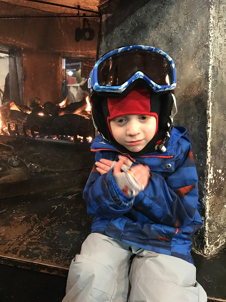 Day 1 (12/29/2017): Connor warming up by the fire at Waterville Valley after skiing