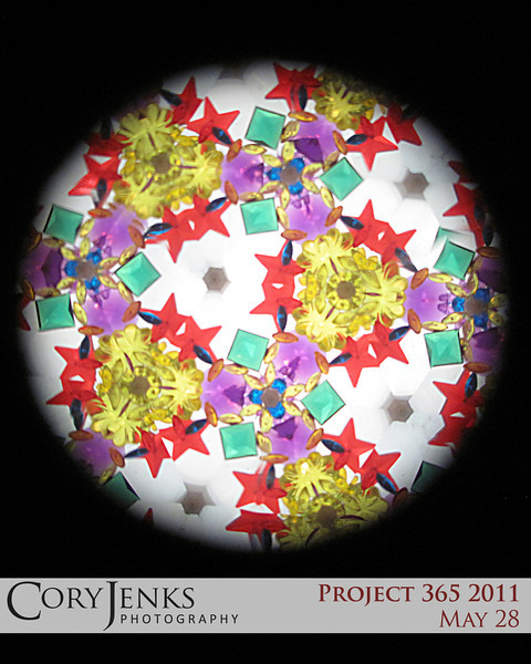 Project 365: May 28 - Kaleidoscope. A kaleidoscope is a circle of mirrors containing loose, colored objects such as beads or pebbles and bits of glass. This one was taken at Grand Rabbit's toys.