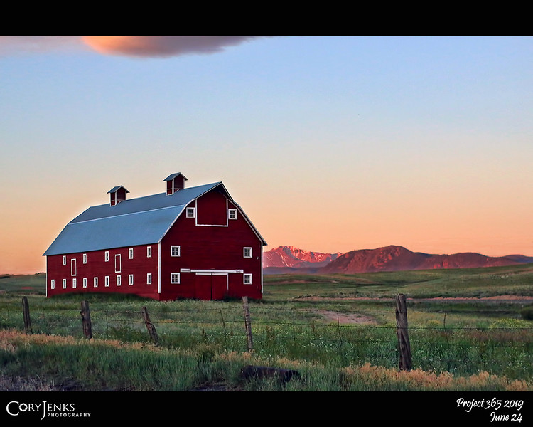 2019 Project 365: June 24 - Barn and Peak<br /> <br /> I have always been fond of barns and the lifestyle they represent. I have shot this barn before, but it captures my attention every time I pass by. This was taken at 5:50 in the early morning with the sunrise lighting Pikes Peak in the background.