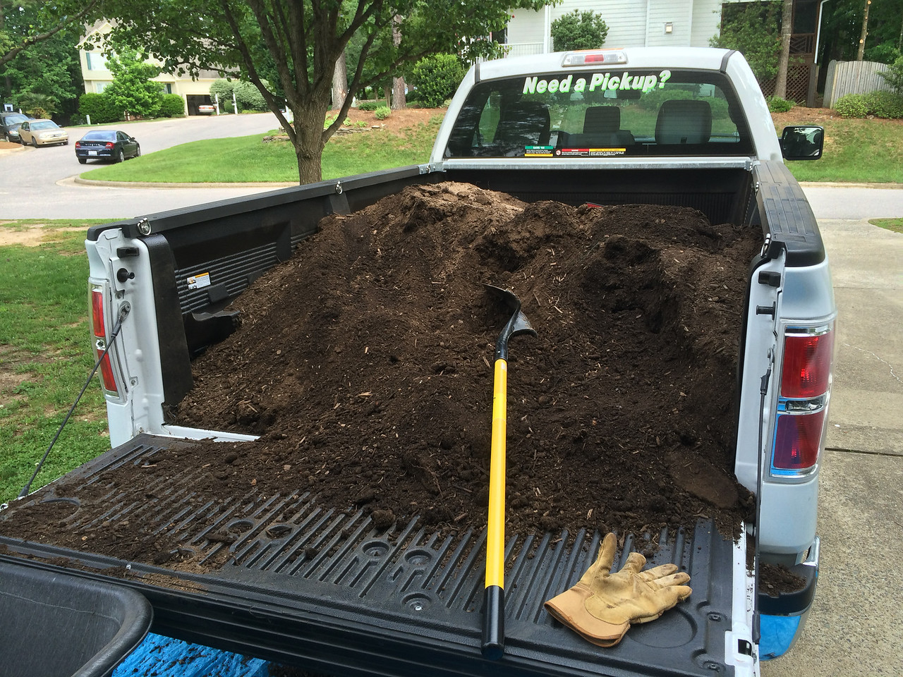 This is what one and a half cubic yards of 50/50 (50% landscape soil, 50% compost) from Mulch Masters looks like. <br /> <br /> A local U-Haul place offered 24-hour rental of a Ford F150 for a decent price. They said moving dirt would be okay since it had a bed liner. It even came with a bad pun on the back window, which is always nice. Apparently a full size pickup can carry up to two cubic yards so this much wasn't a problem.<br /> <br /> It was a lot of dirt and it took a long time to move to the beds, one wheelbarrow full at a time. (Safety tip: a wheelbarrow full of dirt is very heavy and you don't want to be on the downhill side of it.) It took about four hours (?) to move all the dirt. Hosing down the truck afterward took an hour since dirt hides in the bed liner crevices.