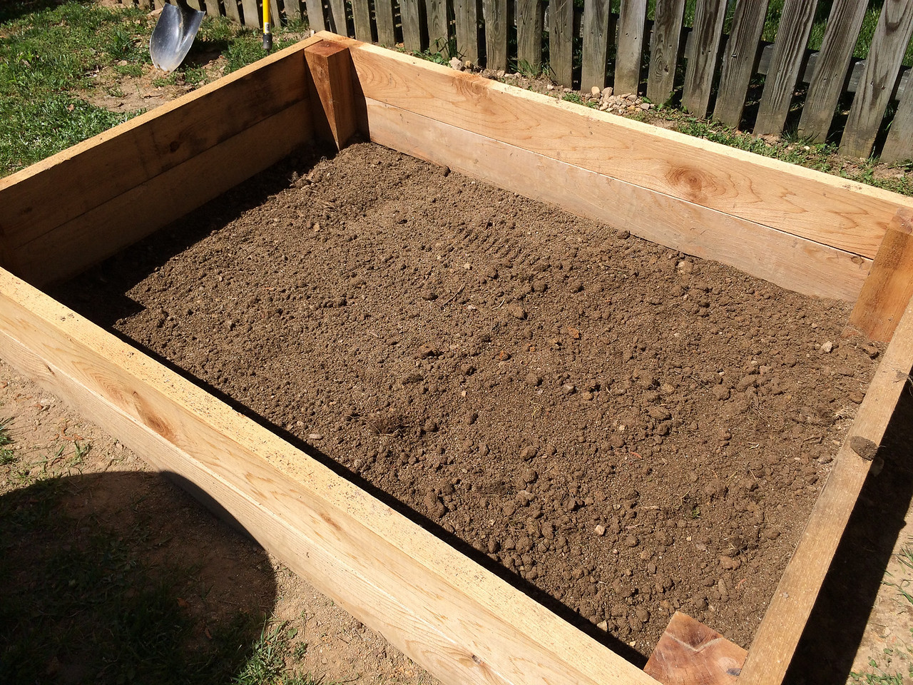 Having learned my lesson, I carefully prepared the second bed for laying the hardware cloth. Shoveled out enough dirt so I could rake the ground flat, leaving 90 degree angles everywhere. I also made sure not to step in the bed after this point.