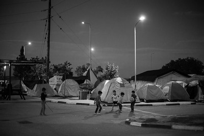 Kids always find ways to entertain themselves and make the best of the worst situations. They spend their days (and nights) playing around in the best cases but also lose time for their education.  Eko Petrol station Camp, Polykastro area, Greece. May 2016.