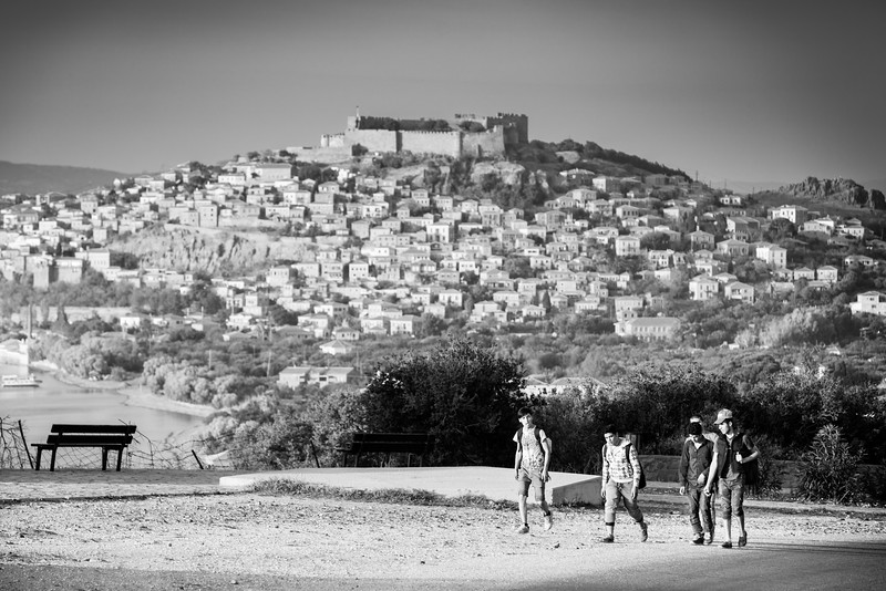 Refugees walking in the hills on Lesvos with Molyvos town and castle in the background. Lesvos is a magnificent place and relies heavily on tourism thanks to all the majestic landscapes. It always makes a sharp contrast to see such difficult human situations in these impressive sights.