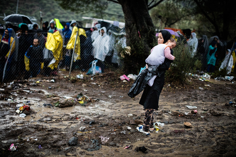 A mother holds her daughter in Moria camp in front of the queue. Even in the pouring rain, refugees had to wait outside to register if they did not want to lose their turn. The conditions in the camp were inadequate for human dignity.