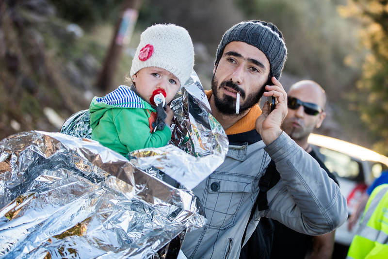 A man carries his daughter in an emergency blanket while calling his family after arriving on the shores of Lesvos on Skala Sikamineas. After celebrating, the first thing refugees usually do on arriving is calling their family and friends back home or on the Turkish side to tell them that they are safe and in Europe. Most refugees have smart phones which are incredibly useful for them; reaching to family, searching for relatives online, looking up information about the road ahead and taking pictures that are not only souvenirs but can prove vital for them. It is important to remember that most refugees are not economic refugees and are thus  from the middle class and can afford smart phones. They are not fleeing poverty, they are fleeing war and insecurity.