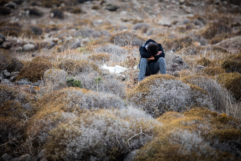 A man waits in the hills next to the shores of Lesvos island where he just arrived.