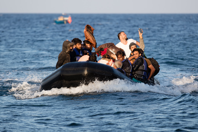 A boat full of refugees  arrives from the Turkish coast. A man smiles while taking a selfie before reaching the shore. When everything goes well, refugees are happy to arrive and celebrate accordingly. The journey usually takes two hours and the boats are handled by a refugee which will have  received very basic instructions on how to operate it and where to go. The smugglers do not care  about well-being of refugees and will often threaten them at gunpoint if refugees refuse to leave when weather conditions are too harsh. It's not unusual to see injured refugees arriving on the island after confrontations with smugglers. Lesvos Island, Greece.