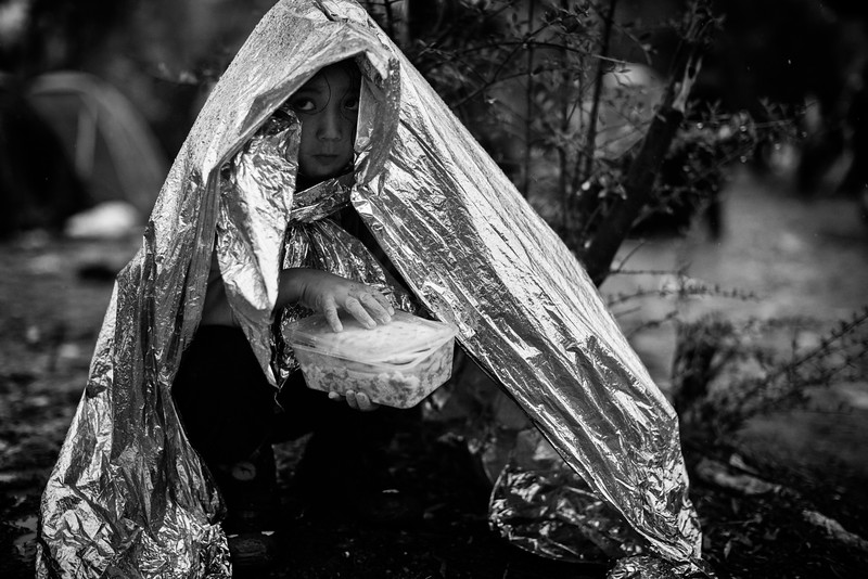 A girl tries to protect herself from the rain under an emergency blanket in the registration camp of Moria. Before pursuing their journey to Athens, all refugees must register themselves. This can prove to be a hard time as waiting can be anywhere from a couple of hours to more than three days. Situation is always changing in the camp but when this picture was taken, it had been raining for three days and most refugees had barely any shelter from the pouring rain.