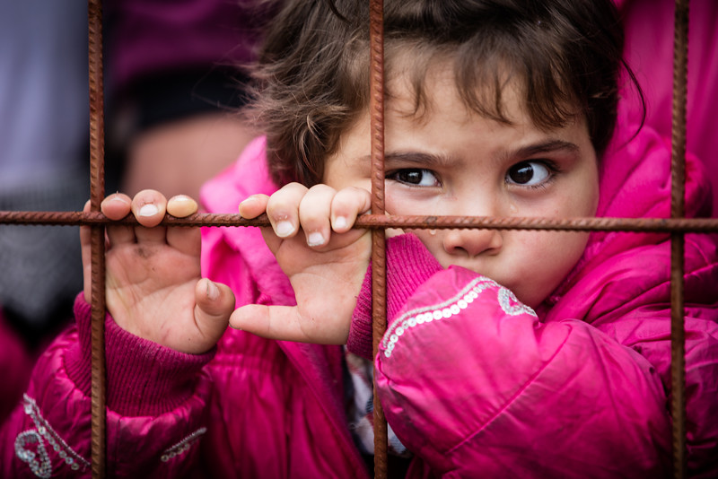 Stuck outside in the crowd attempting to rush into the transit camp of Gevgelija, this little girl cries as she is holding on the fence that separates her from the security of the camp. Gevgelija, Macedonia (FYROM).
