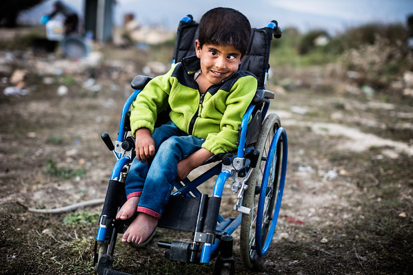 An handicapped little boy is left alone outside of the refugee camp where he lives. Bekaa Valley, Lebanon.