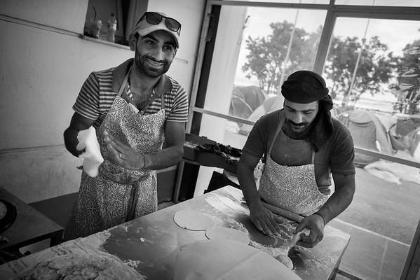 Syrian bakers at work in their improvised bakery in the temporary refugee camp of EKO petrol station.<br /> EKO camp, Polykastro, Greece. 2016.<br /> ----<br /> Des boulangers syriens à l'oeuvre dans leur nouvelle boulangerie improvisée au milieu du camp de réfugiés de la station d'essence d'EKO.<br /> Camp d'EKO, Polykastro, Grèce. 2016