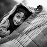 A boy hides from the  rain under a blanket with his mother in Moria registration camp. Lesvos Island, Greece, 2015 ---- Un jeune garcon se protège de la pluie sous une couverture avec sa m� ...