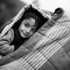 A boy hides from the  rain under a blanket with his mother in Moria registration camp.<br /> Lesvos Island, Greece, 2015<br /> ----<br /> Un jeune garcon se protège de la pluie sous une couverture avec sa mère dans le camp d'enregistrement de Moria.<br /> Ile de Lesbos, Grèce, 2015
