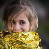 Young refugee resting in an emergency blanket after getting off the boat.<br /> Lesvos Island, Greece, 2015<br /> ----<br /> Jeune réfugiée se reposant dans une couverture d'urgence après être débarquée du bateau.<br /> Ile de Lesbos, Grèce, 2015