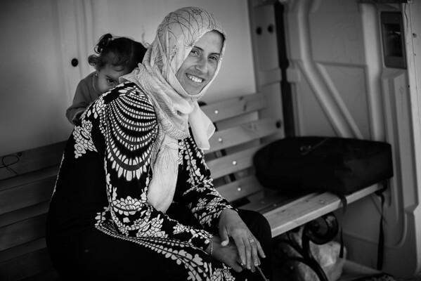 Young girl playing hide and seek from the photographer with her mother.<br /> Kara Tepe camp, Lesvos Island, Greece. 2016.<br /> ----<br /> Jeune fille jouant à cache-cache avec le photographe dans un camp de réfugiés.<br /> camp de Kara Tepe, Ile de Lesbos, Grèce. 2016