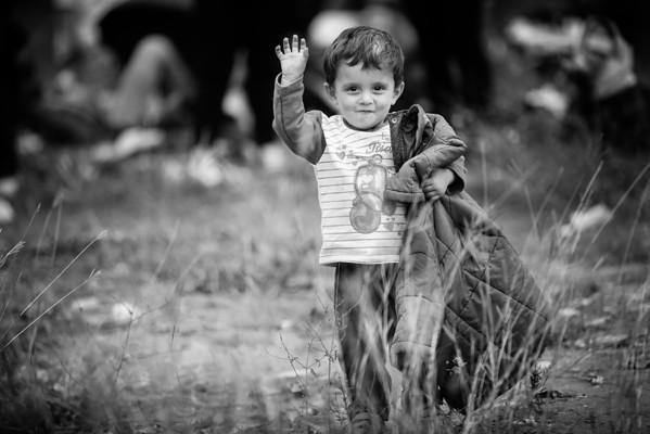 Stopping to wave at the photographer on the way to the transit camp past the Greek border.<br /> Gevgelija, Macedonia, 2015<br /> ----<br /> Pause pour saluer le photographe en route vers le camp de transit près de la frontière grecque.<br /> Gevgelija, Macédoine, 2015