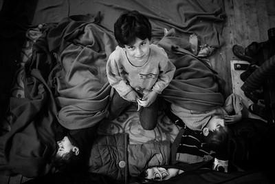 A young boy keeps watch over his two sleeping brothers in a registration camp. Berlin, Germany, 2015 ---- Un jeune garçon veille sur ses deux frères assoupis dans un camp d'enregistrement. Berlin, Allemagne, 2015