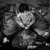 A young boy keeps watch over his two sleeping brothers in a registration camp.<br /> Berlin, Germany, 2015<br /> ----<br /> Un jeune garçon veille sur ses deux frères assoupis dans un camp d'enregistrement.<br /> Berlin, Allemagne, 2015