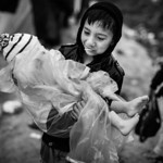 A boy protects his younger brother from the rain in Moria camp. Lesvos Island, Greece, 2015 ---- Un grand fr�re prot�ge son plus jeune fr�re de la pluie � travers le camp de Moria. Ile d ...
