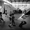Children having fun in their new home of an official military camp following the dismantling of Idomeni camp.<br /> Oreokastro camp, Thessaloniki area, Greece. 2016.<br /> ----<br /> Des enfants s'amusent dans leur nouveau chez-soi d'un camp de réfugiés officiel de l'armée grecque suite au démantèlement du camp d'Idomeni.<br /> camp d'Oreokastro, Thessaloniki, Grèce. 2016