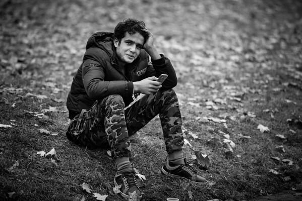 Young man on the phone in Berlin park under the autumn leaves.<br /> Berlin, Germany, 2015<br /> ----<br /> Jeune homme au téléphone dans un parc de Berlin sous les feuilles d'automne.<br /> Berlin, Allemagne, 2015