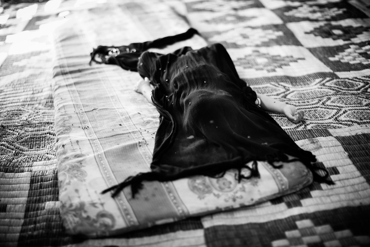 A baby sleeps on the carpet in the middle of a tent. The shawl covers him from the flies around. Akkar District, Lebanon