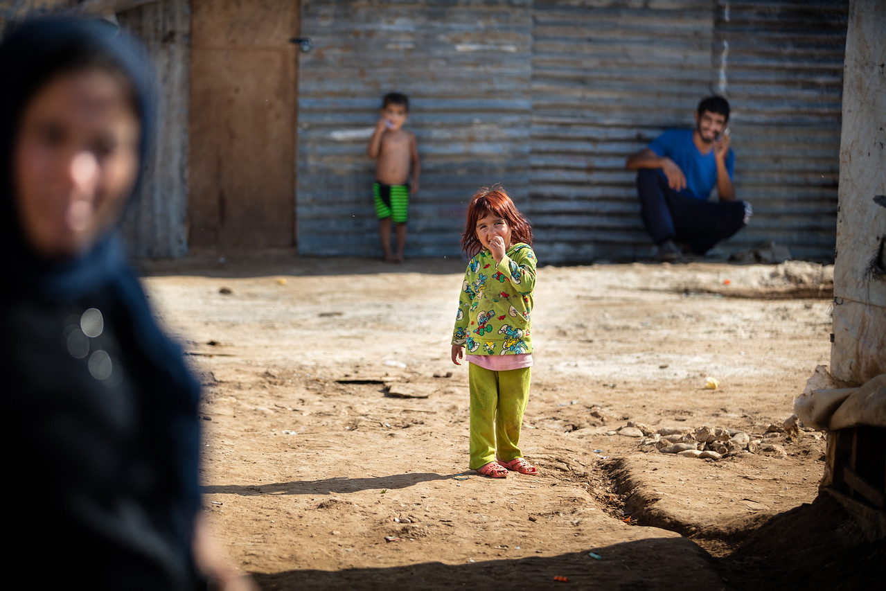 Among her relatives, a little girl smiles at the camera. Around 20 families live in the camp that has been reestablished in this location for one year. Akkar District, Lebanon