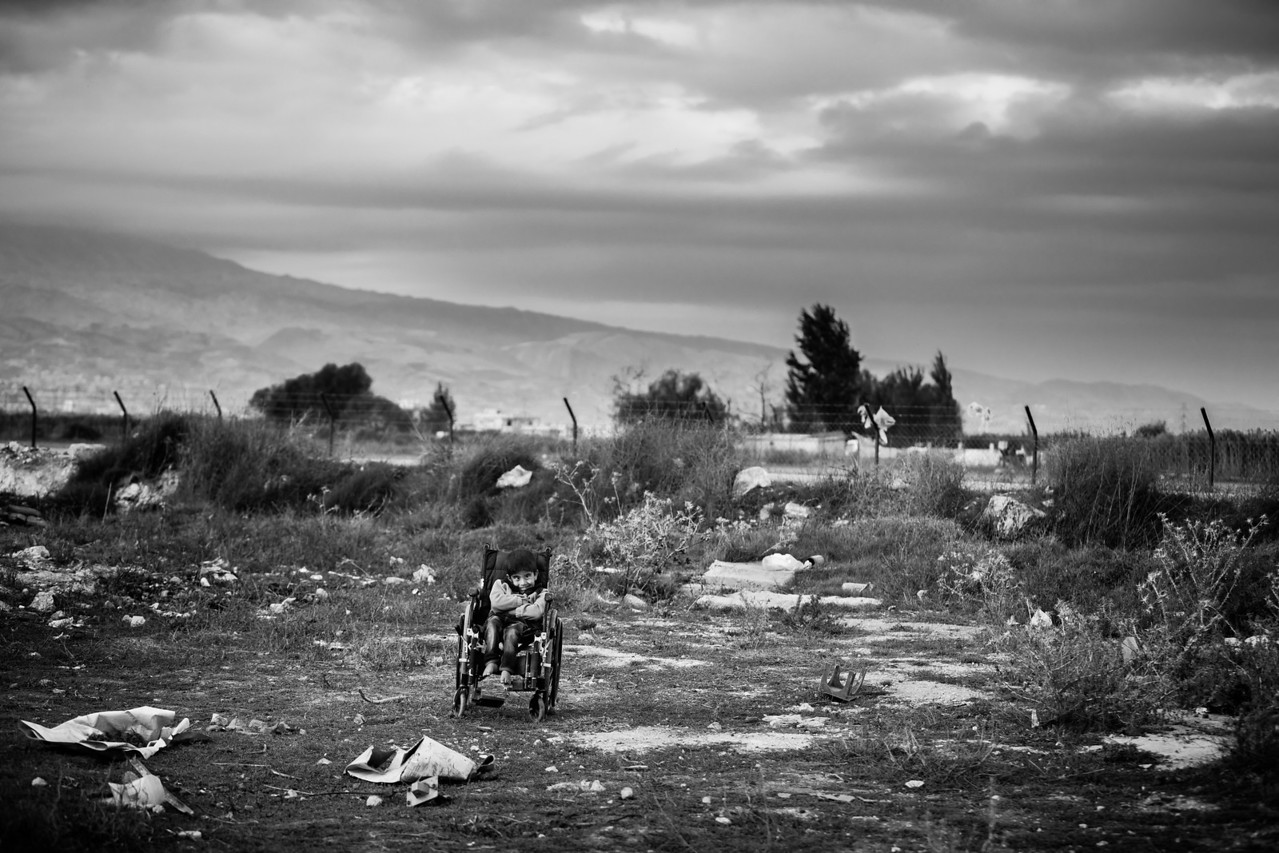 An handicapped child is left alone on his wheelchair in the middle of the field next to the refugee camps in the Bekaa Valley, Lebanon. He is still smiling.