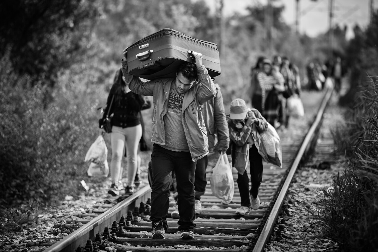 Family walking behind him and material objects weighing on his shoulder, this man walks on the rails towards the Serbian border like so many others with everything he has, onward to a new and hopefully better life. Serbia-Macedonia (FYROM) border.