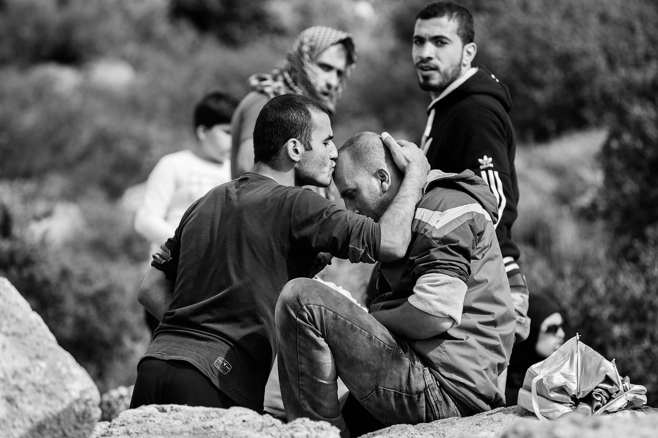 One man kisses his friend on the head. The refugees are thankful and glad to be safe and on their way to a better lives. Oxy camp, Lesvos Island, Greece.