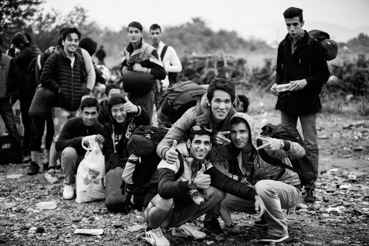 A group of young men traveling together takes time to enjoy their journey and pose along the way. Single men alone often get together and become friends on the way. Gevgelija, Macedonia (FYROM).
