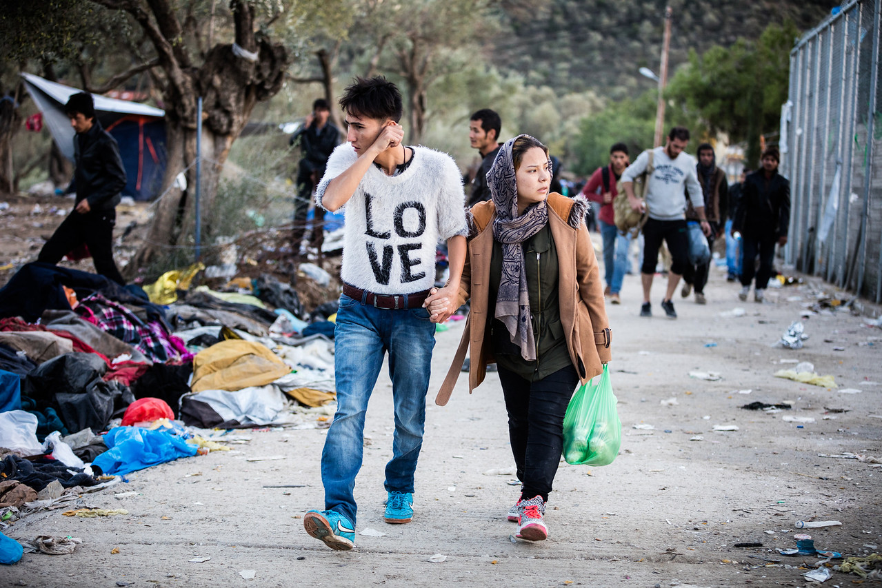 A young couple walks towards the hope of building a new life together and raising a family in a safe environment. Moria Camp, Lesvos Island, Greece.