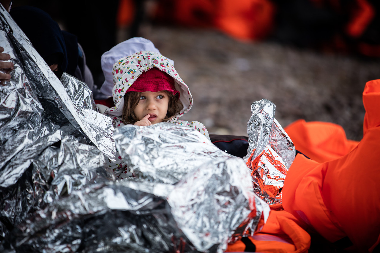 A little girl is wrapped in thermal blankets as she recovers from the perilous crossing of the Aegean Sea. Her family is mourning as one of the women drowned while getting off the boat. Skala Sikamineas, Lesvos Island, Greece.