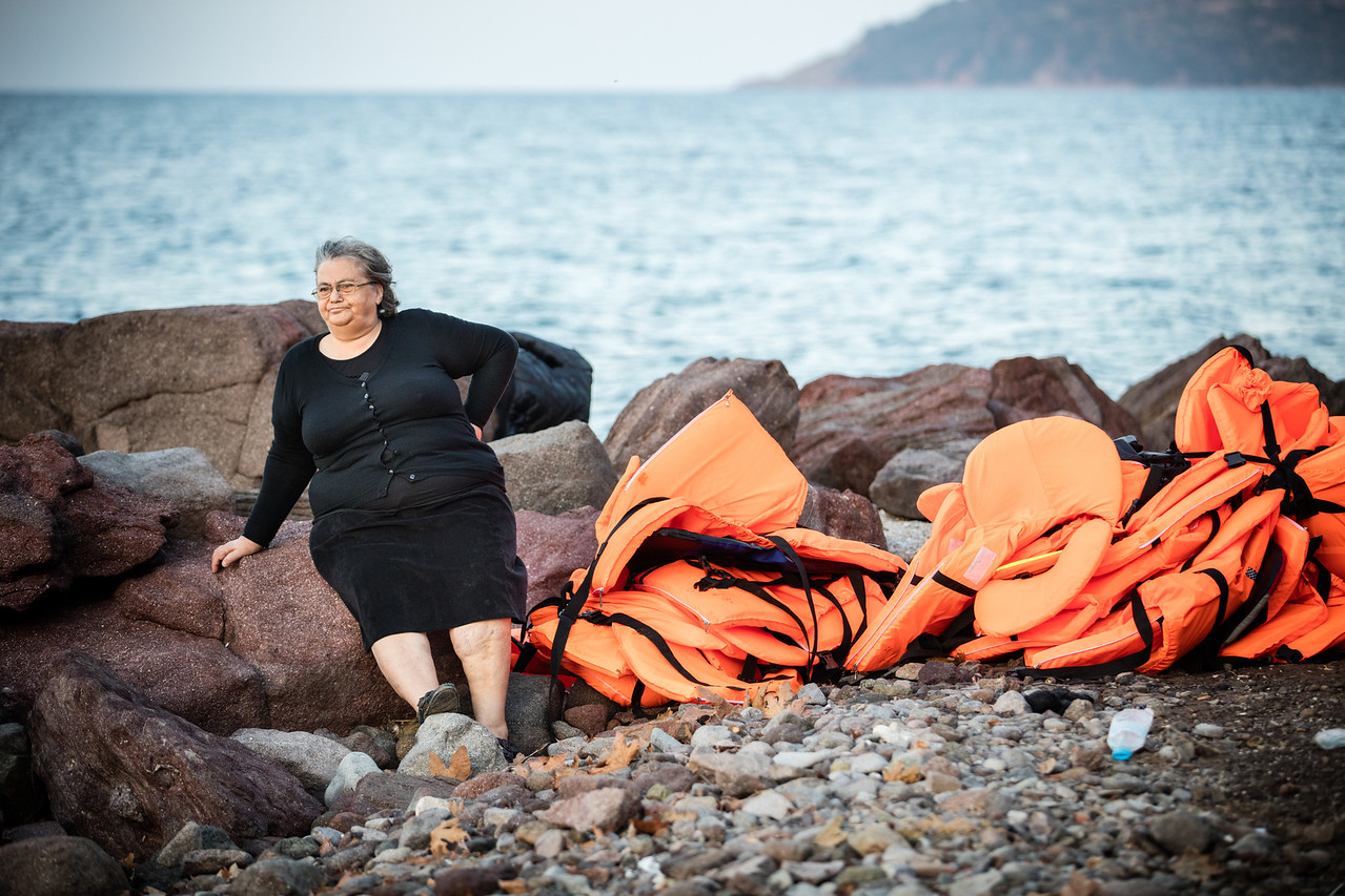 A Greek lady living on the island watches refugees arriving among life jackets. Conflicts between refugees and locals are happening more and more as the locals think they might be threatening their island.