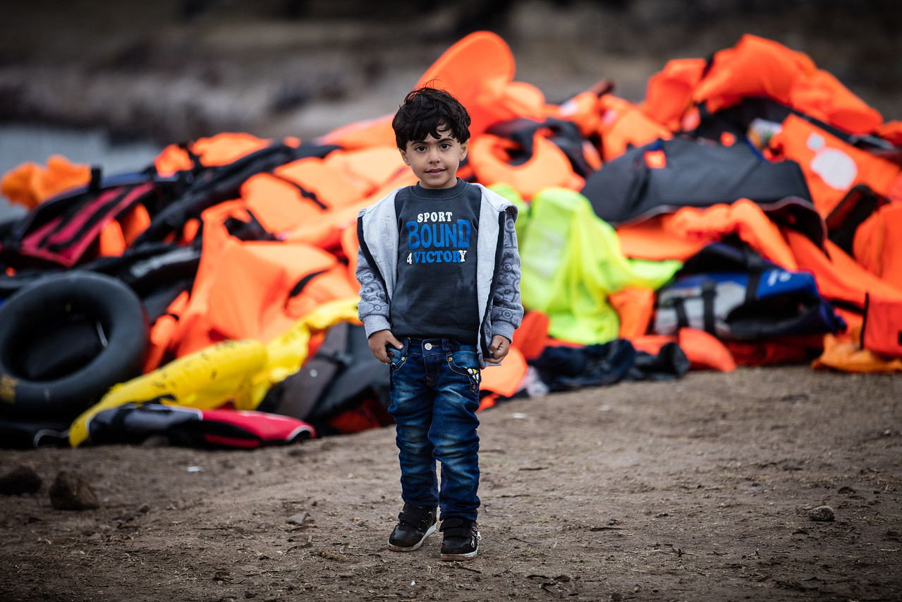 A little boy in front of a mountain of discarded life jackets. Each arriving boat represents an important amount of trash; the boat in itself is made of a lot of plastic and each of the 50 refugees wears a life jacket. Refugees have no means of carrying the wet and useless life jackets anywhere and they are left on the beaches.