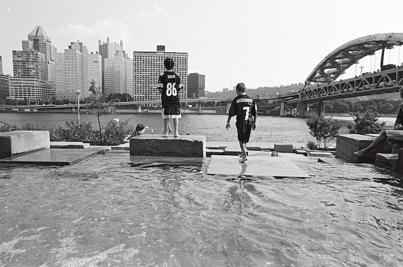 Before a preseason game, children try to cool off by playing in fountain along Riverside Park. Pittsburgh. 2005. [02980023]