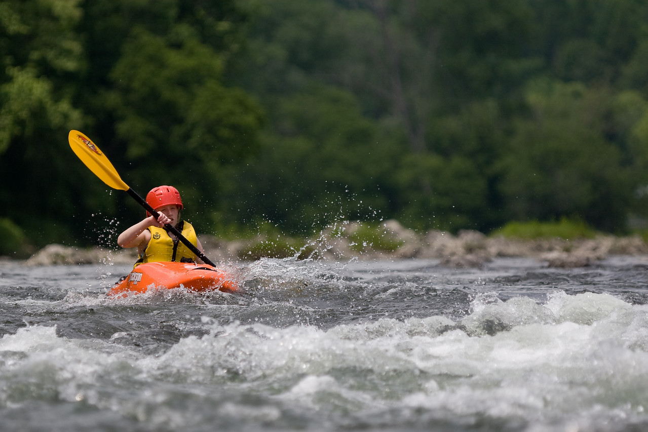 A young white water paddler approaches the rapids on the White River near Sharon, Vermont